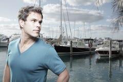 Mann an einem Jachthafen, der über seiner Schulter flüchtig blickt Lizenzfreie Stockfotografie