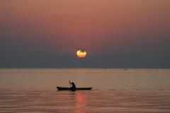Mann in einem Kanu am Sonnenaufgang Stockbild
