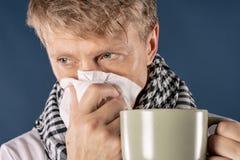 Mann in einem karierten Schal mit großem Becher und Gewebe auf blauem Hintergrund Kalte und Grippekrankheitsentlastung stockfoto