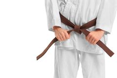Mann in einem Kimono und in einem Gurt für Kampfkünste auf dem weißen Hintergrund stockfotografie