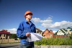 Mann in einem orange Sturzhelm mit dem Plan des Aufbaus Lizenzfreie Stockbilder