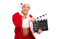 Mann in einem Sankt-Kostüm, das ein clapperboard hält Lizenzfreie Stockbilder