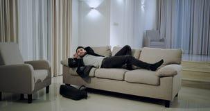 Mann in einem schwarzen Anzug, der zu Hause von der Arbeit er niederlegend auf dem Sofa und die Fernsehdirektübertragung und -sc stock footage