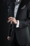 Mann in einem schwarzen Anzug mit einer Zigarre Lizenzfreies Stockbild