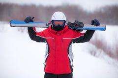 Mann in einem Skianzug mit Skis Stockfotografie