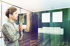 Mann in einem Sofa und Posterwohnzimmer verdoppeln Seite Stockfoto