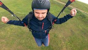 Mann in einem Sturzhelm handhabt seinen Gleitschirm Gleitschirmfliegen stock footage