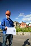 Mann in einem Sturzhelm mit dem Plan des Aufbaus Stockfotografie