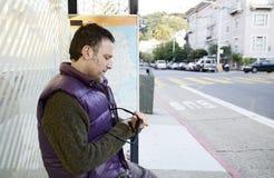 Mann an einer Bushaltestelle Stockfoto
