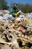 Mann in einer Gasmaske, die auf dem Abfall sitzt und einen Knochen hält Lizenzfreie Stockfotos