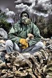 Mann in einer Gasmaske, die auf dem Abfall sitzt und einen Knochen hält Lizenzfreies Stockfoto