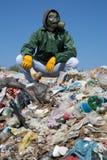 Mann in einer Gasmaske, die auf dem Abfall sitzt und einen Knochen hält Stockfotografie