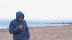 Mann in einer Jacke auf dem Strand durch das Meer mit einem Handy Winter in Meer stock video footage