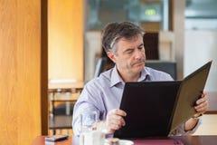 Mann in einer Kaffeestube, die das Menü betrachtet lizenzfreie stockfotografie