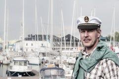 Mann in einer Kappe des Seemanns auf der Plattform eines Segelboots Lizenzfreies Stockfoto
