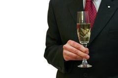 Mann in einer Klage, die ein Glas Champagner mit a anhält lizenzfreies stockfoto