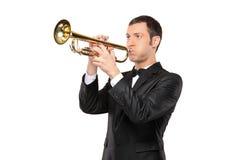 Mann in einer Klage, die eine Trompete spielt Stockbild
