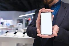 Mann in einer Klage hält in seinen Händen einen modernen Smartphone mit einem weißen Schirm stockfotografie