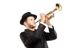 Mann in einer Klage mit einem Hut, der eine Trompete spielt Lizenzfreies Stockfoto