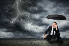 Mann in einer Klage und in einem Regenschirm sucht Schutz von einem Sturm Lizenzfreies Stockfoto