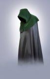 Mann in einer mittelalterlichen Haube und in einem Mantel im Nebel Lizenzfreies Stockfoto