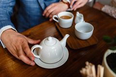 Mann in einer modernen Klage gießt Tee von einer Teekanne in einem Becher Regeln der Etikette in einem Café Mann kümmert sich um  lizenzfreie stockfotos
