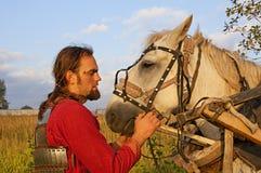 Mann in einer Rüstung und in einem weißen Pferd Stockfotografie