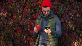 Mann in einer roten Kappe mit einer Schale in seinen Händen trinkt Tee oder Kaffee draußen und benutzt einen Smartphone an einem  stock video footage