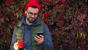 Mann in einer roten Kappe mit einer Schale in seinen Händen trinkt Tee oder Kaffee draußen und benutzt einen Smartphone an einem  stock footage