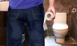 Mann in einer Toilette, die Seidenpapierrolle hält Stockbild