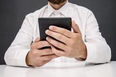 Mann in einer weißen Hemdlesung auf einem Leser oder einer Tablette stockfotografie