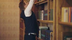 Mann in einer Weste wählt ein Buch von einem Bücherregal in einer Bibliothek Reifer Mann mit ernstem Gesicht Professor steht in g stock video footage