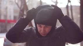 Mann in einer Winterjacke und -hut ist stehende Außenseite in einer kalten Stadt, die draußen eingefroren wird stock video