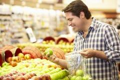 Mann-Einkaufen für Erzeugnis im Supermarkt lizenzfreie stockbilder