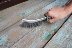 Mann entfernen die alte Farbe von der Holzoberfläche mit Drahtbürste Stockfotografie