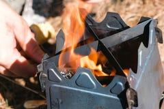 Mann entflammt Metalllager-Ofenofen auf Holz draußen Männer ` s übergibt Nahaufnahme Beschneidungspfad eingeschlossen stockbilder