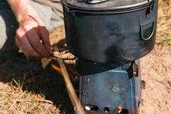 Mann entflammt Metalllager-Ofenofen auf Holz draußen, um eine Nahrung zu kochen Männer ` s übergibt Nahaufnahme lizenzfreie stockfotos