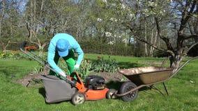 Mann entladen Schnittgras in Karren Rasen, der im Frühjahr mäht 4K stock video footage