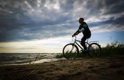 Mann entlang dem Ufer mit dem Fahrrad Lizenzfreie Stockfotos