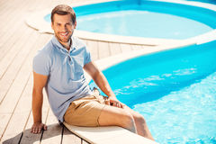 Mann entspannender Poolside Stockfotos