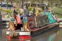 Mann entspannt sich auf Heck von narrowboat in der Sonne Lizenzfreie Stockbilder