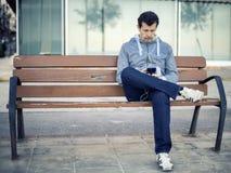 Mann entspannter ussing Smartphone auf einer Bank Lizenzfreie Stockfotos