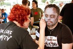 Mann erhält Zombie-Umarbeitung vom Maskenbildner Lizenzfreie Stockfotografie