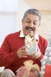 Mann erregt, um Weihnachtsgeschenk zu öffnen Lizenzfreies Stockfoto