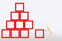 Mann errichtet einen Bau als Pyramide Stockfoto