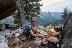 Mann errichtete ein Lagerfeuer im Wald in der Natur Überleben Sie in den Bergen im Wald und in einer Topfwanne über einem Lagerfe lizenzfreie stockbilder