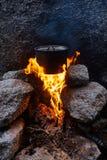 Mann errichtete ein Lagerfeuer im Wald in der Natur Überleben Sie in den Bergen im Wald und in einer Topfwanne über einem Lagerfe lizenzfreies stockbild