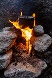 Mann errichtete ein Lagerfeuer im Wald in der Natur Überleben Sie in den Bergen im Wald und in einer Topfwanne über einem Lagerfe lizenzfreie stockfotografie