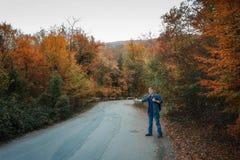 Mann fährt auf der Straße per Anhalter lizenzfreies stockbild