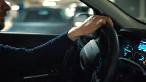 Mann fährt Auto durch einen Parkplatz und sucht nach einer Parkmöglichkeit stock footage